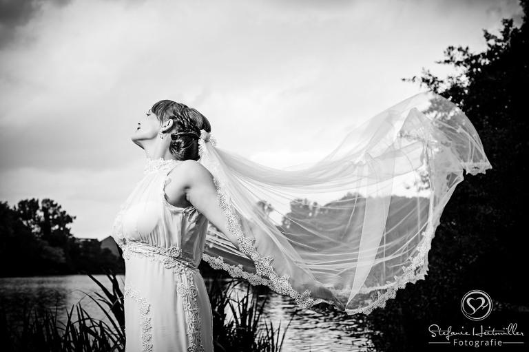 Ein langer Schleier einer Braut schwebt bei Hochzeitsfotos im Wind.